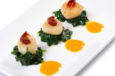Sea scallops with spinach and tomatoes — Stock Photo