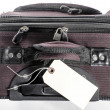 Worn suitcase with tag — Stock Photo
