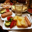 Stock Photo: Boiled potatoes with sausages. Glass of vodka.