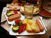 Boiled potatoes with sausages. Glass of vodka. — Stock Photo