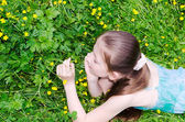The child the girl lies on a glade with flowers — Stock Photo