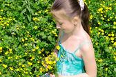 The child sits on a glade and holds flowers — Stock Photo