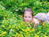 The child the girl has a rest on a glade with flowers — Stock Photo