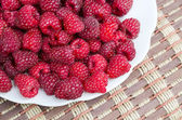 Raspberry in a plate on a table — Stock Photo