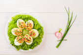 Stuffed eggs on lettuce with chives garnish — Stock Photo