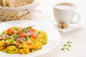 Scrambled eggs and bacon on white table — Stock Photo