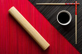 Chopsticks and bowl with soy sauce on bamboo mat — 图库照片