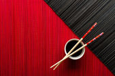 Chopsticks and bowl with soy sauce on bamboo mat — Stock Photo