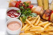 Chips and skewers on a white plate — Stock Photo
