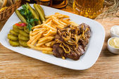 Roast beef, french fries and jug of beer — Stock Photo