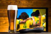 Glass of beer and tv remote, football match in background — Stock Photo