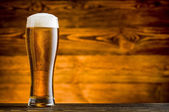 Glass of beer on wooden table and wooden background — Stock Photo