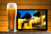 A glass of cold beer on the table, football match in background — Stock Photo