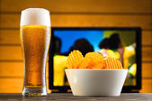 Glass of cold beer and chips, football match in background — Stock Photo