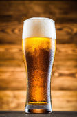Glass of cold beer on wooden table — Stock Photo