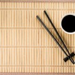 Chopsticks and bowl with soy sauce on bamboo mat — Stock Photo #50266597