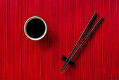 Chopsticks and bowl with soy sauce on bamboo mat — Foto de Stock