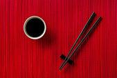 Palillos y tazón con salsa de soja sobre la estera de bambú — Foto de Stock