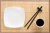 Chopsticks, white plate and bowl with soy sauce on bamboo mat — Stock fotografie