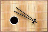 Chopsticks and bowl with soy sauce on bamboo mat — Foto Stock