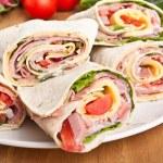 Wrapped tortilla sandwich rolls cut in half — Stock Photo #41983087