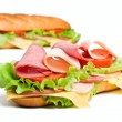 Two halves of long baguette sandwich with lettuce, tomatoes, ham — Stock Photo
