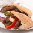 Two halves of pita bread sandwich with meat and vegetables on a — Stock Photo