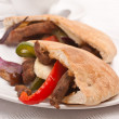 Two halves of pita bread sandwich with meat and vegetables on a  — Stock Photo #41983975