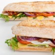 Two halves of long white wheat baguette sandwich — Stock Photo