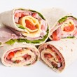 Stack of wrapped tortilla sandwich rolls cut in half — Stock Photo