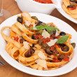 Stock Photo: Linguine pastwith fresh tomato puttanescsauce, grated parmes