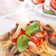 A bowl of pasta linguine with mushrooms, tomato sauce and parmes — Stock Photo