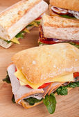 Ciabatta bread sandwich stuffed with meat, cheese and vegetables — Stock Photo