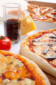 Three different kinds of pizza and a glass of cola — Stock Photo