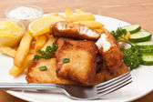 Fish and chips on a plate on a wooden table — Stock Photo