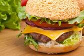 Duże smaczne cheeseburger na drewnianym stołem — Zdjęcie stockowe