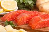 Three fresh salmon pieces with lemons on a cutting board — Stock Photo