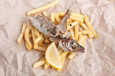 Fish and fries on a piece of brown craft paper — Stockfoto