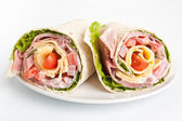 Wrapped tortilla sandwich rolls cut in half — Stock Photo
