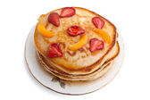 Stack of pancakes with syrup and fruit on a plate — Stock Photo