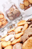 Big pile of various cookies with three cookie jars at the back — Stock Photo
