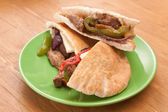 Three halves of pita bread sandwiches with meat and vegetables — Stock Photo
