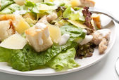 Traditional caesar salad on white plate with a fork — Stock Photo