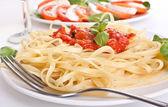 Linguine pasta with fresh tomato sauce and basil — Stock Photo