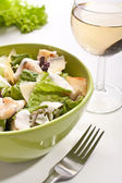 Traditional caesar salad with a glass of white wine — Stock Photo