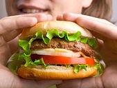 Man holding a hamburger — Stock Photo