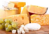 Big group of cheeses with white grapes — Stock Photo