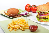 Two big cheeseburgers and french fries with tomatoes and ingredi — Stock Photo