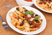 Linguine pasta with fresh tomato puttanesca sauce, grated parmes — Stock Photo