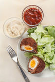 Scotch eggs cut in halves on a plate — Stock Photo
